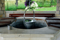 Water well. Bucket full of fresh water, water cup and an old water well royalty free stock photo
