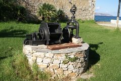 Water well with antique water pump. Royalty Free Stock Image