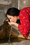 Water well in Bulgaria. And a young woman in traditional dress drinking, in the old village of Jeravna Royalty Free Stock Photos