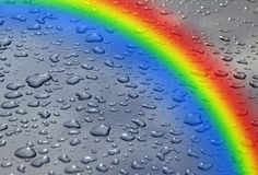 Water wet rain raindrops dew on glass rainbow background colours weather raining stock image