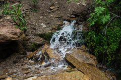 Water on wet stones and grass. The flow of water on wet stones and grass Royalty Free Stock Photography