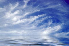 Water world. A digital composite of endless ocean reflecting feathery clouds in deep blue sky Stock Image