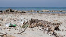 Waterblikken en plastic flessen op het zandige strand Strandverontreiniging Langzame Motie stock videobeelden