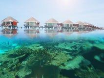 Waterbungalowwen in een het eilandtoevlucht van de Maldiven met onderwaterkoraalriffen stock afbeeldingen