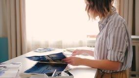 Watercolor artwork female turning sketchbook pages. Watercolor artwork. Yong blonde female sitting at workplace turning sketchbook pages. Professional stock footage
