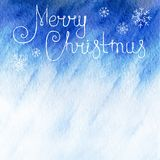 Watercolor background. Blue sky with falling snowflakes and text Merry Christmas. Winter watercolor background. Blue sky with falling snowflakes and text Merry Royalty Free Stock Images