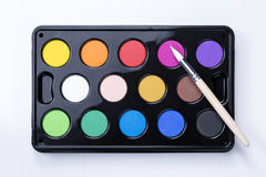Watercolor box and brush Stock Photos