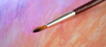 Watercolor and brush. Brush laying on a aquarel painting Royalty Free Stock Photo