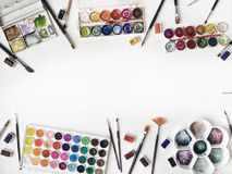 Watercolor and brushes at white background. Flat lay Royalty Free Stock Images