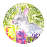 Watercolor bunny sitting under the Christmas tree with gifts snowing. Watercolor bunny sitting under the Christmas tree with Christmas gifts Royalty Free Stock Photography