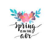 Watercolor card with flowers and stylish lettering - `spring is in the air`. Stock Photo
