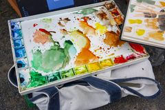 Colorful used water color pallette with blotches of paint patterns and markings stock photography
