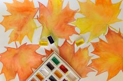 A watercolor drawing with bright autumn maple leaves and a set of colors Royalty Free Stock Photo