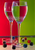 Watercolor Duo. Two glasses filled with water, surrounded by multicolored dice, and set against a duo colour, backdrop Stock Photos