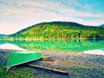 Watercolor effect. Abandoned fishing paddle boat on bank of Alps lake. Morning lake Stock Image