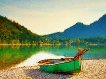 Watercolor effect. Abandoned fishing paddle boat on bank of Alps lake. Morning lake Royalty Free Stock Images