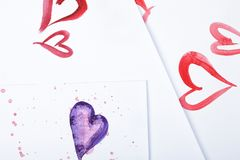 Watercolor hearts and colorful watercolor blots on white paper. Royalty Free Stock Photo