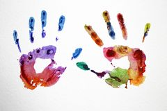 Multi-colored watercolor handprints. Watercolor multicolored prints of hands on a white sheet of paper Stock Illustration