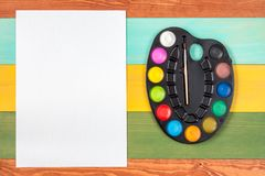 Watercolor paint and blank paper sheet Royalty Free Stock Photography