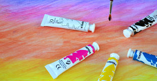 Watercolor paint and brush. Paint tubes and brush on a painting.School painting materials Stock Photography