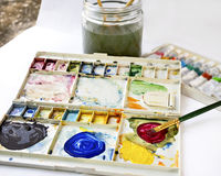 Watercolor paint and brush in white box, palette  on white backg Stock Image