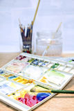 Watercolor paint and brush in white box,palette on wood table. Stock Photos