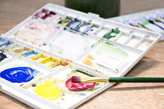 Watercolor paint and brush in white box,palette  on wood table. Stock Photography