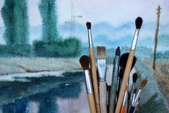Watercolor paint brushes against aquarelle background stock images