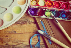 Watercolor paint, brushes, old album and palette Stock Images
