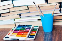 Watercolor paint, brushes well used and sheet of paper on wooden table with stack of books background