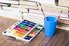 Watercolor paint, brushes well used on wooden table with stack of books background