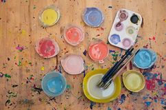 Watercolor paint and paintbrush on light colored wood. Plastic containers of watercolor paint and thin paint brushes in water on a light wood table Royalty Free Stock Photos