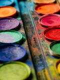 Watercolor paint palette closeup. Photo of a palette of watercolor paints on a well-used tray Stock Photo