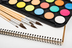 Watercolor paint set and new brushes with clean paper Stock Photos