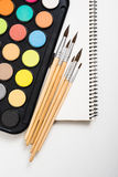 Watercolor paint set and new brushes with clean paper. On artist's work desk, creative artistic tools on white background closeup royalty free stock image