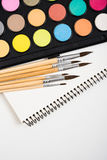 Watercolor paint set and new brushes with clean paper. On artist's work desk, creative artistic tools on white background closeup royalty free stock images