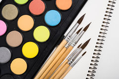 Watercolor paint set and new brushes with clean paper. On artist's work desk, creative artistic tools on white background closeup royalty free stock photo