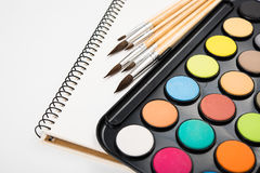 Watercolor paint set and new brushes with clean paper. On artist's work desk, creative artistic tools on white background closeup stock image