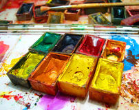 Watercolor painting and artistic tools on table Royalty Free Stock Images