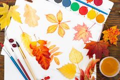 Watercolor painting with autumn leaves, paint, brushes and color Royalty Free Stock Image