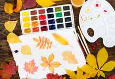 Watercolor painting with autumn leaves, paint, brushes, palette Stock Photography