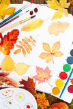 Watercolor painting with autumn leaves, paint, brushes, palette Royalty Free Stock Images