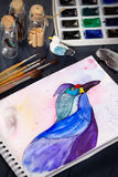 Watercolor painting of blue bird and artistic tools on table. Still life composition of artistic workplace stock image