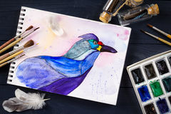 Watercolor painting of blue bird and artistic tools on table. Still life composition of artistic workplace stock photos