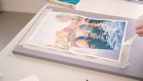 Watercolor painting complete removing duct tape stock footage