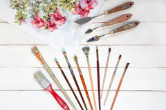 Watercolor painting with different paint brushes and other thing. S on a white wooden background, top view Royalty Free Stock Images