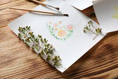 Watercolor painting with flowers on table. Watercolor painting with flowers on wooden table Stock Image