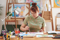 Watercolor painting. Pretty young woman enjoying watercolor painting in art studio stock photos