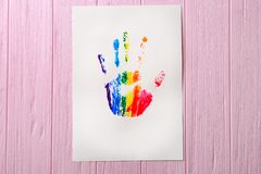 Watercolor painting of rainbow handprint. On wooden background stock photos