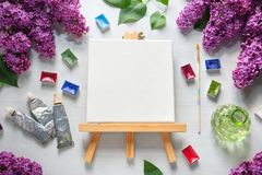 Watercolor paints, brush for painting, paint tubes, empty canvas on easel, watercolor paints and lilac flowers. Top view stock image